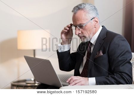 Involved in work. Concentrated involved bearded businessman holding the laptop and sitting in the hotel while working on the project