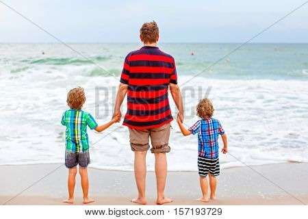 Two happy little kids boys and father standing on the beach of ocean and looking on horizon on stormy day. Family, dad and cute sons making vacations and enjoying summer.