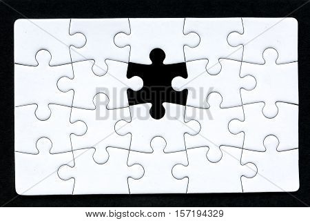 a puzzle that's missing one piece against a black background