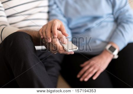 We enjoy television. Pleasant nice aged couple sitting on the settee while watching television and hugging each other
