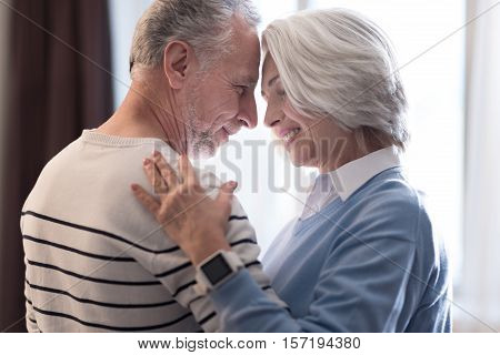 We love each other. Cheerful peaceful aged couple dancing at home while looking at each other and hugging