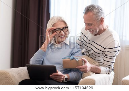 Cute present. Delighted smiling aged man holding a gift while standing near the sofa and hugging his wife