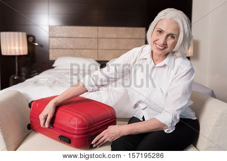 I having trip soon. Smiling happy aged woman sitting on the settee and gathering her luggage for the trip while expressing joy