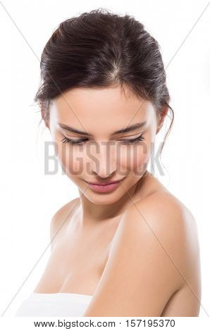 Young beautiful woman with perfect skin looking down. Close up face of beauty young woman. Young beautiful woman feeling shy isolated on white background. Wellness and skin care concept.