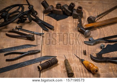 Set of tools for shoemaker on the wooden background. Copy space.