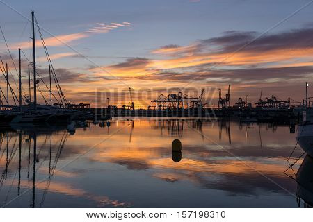 Twilight at Valencia harbor sunrises docked sailboats and cargo port cranes red colors in the sky and water reflection