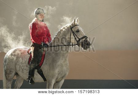 woman in red sitting on gray horse in steam
