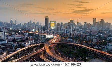 Highway intersection with city business area background during sunset, Bangkok Thailand