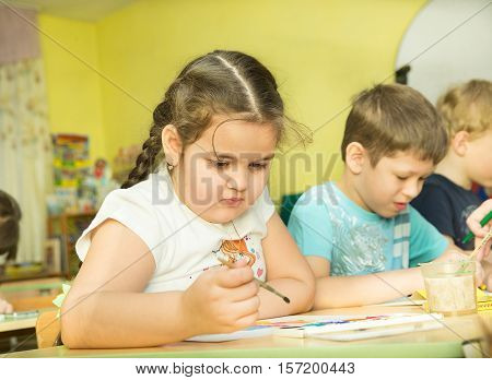 funny children draw paints and pencils brightest pictures in kindergarten - Russia, Moscow - February 04, 2016