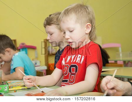 concentrated focused serious boy draw paints and pencils brightest pictures in kindergarten - Russia Moscow - February 04 2016