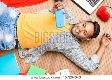 Young indian student taking selfie lying on wooden floor top view at home - Asian man using mobile smartphone relaxing inside the living room - Modern lifestyle concept with cheerful male indoors