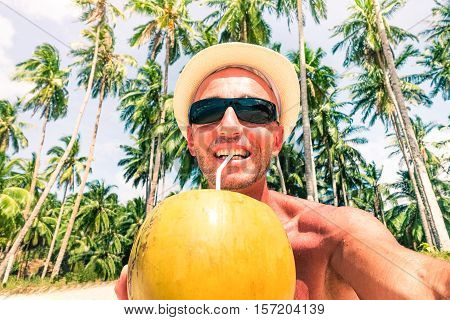 Cheerful man beach selfie drinking coconut milk with palm trees background at tropical island - Middle age male tourist taking self photo on sunny day - Concept of single trip holidays and happiness