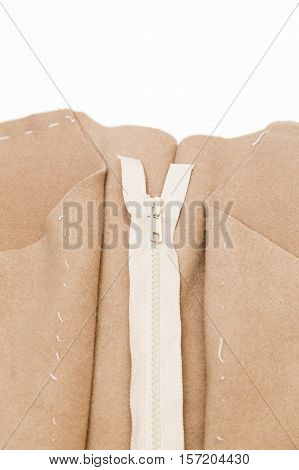Cloth and zipper. Dressmaker prepares wrap detail with sketch lines.