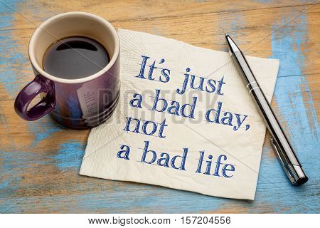 It is just a bad day, not  a bad life - handwriting on a napkin with a cup of espresso coffee