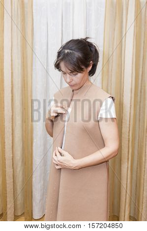Woman being patronized. Dressmaker prepares wrap detail with sketch lines.