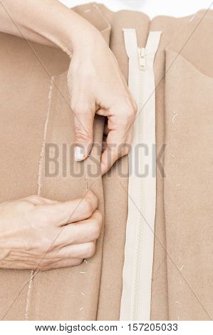 Hands sewing. Dressmaker prepares wrap detail with sketch lines.