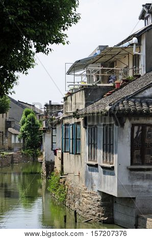 Weathered and old buildings lining the water canals in Luzhi Town in Jiangsu province China.