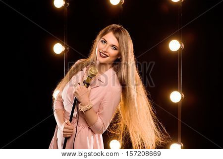 young smily beautiful long hair girl with microphone singing song on the stage in karaoke