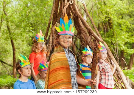 Portrait of cute boy wearing Injun's costume, playing with his friends near his wigwam