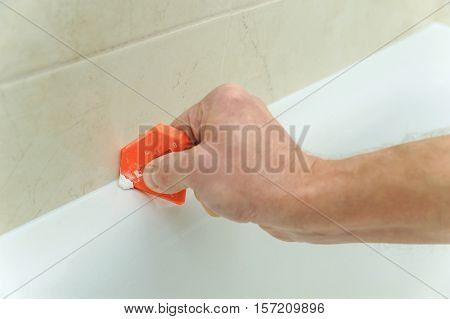 Worker smoothing silicone sealant between the bath and the wall using a spatula.