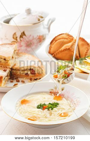 Traditional Tatar holiday table. Tokmach - noodle soup with chicken. Triangles - meat pies and sweet cake. Selective focus
