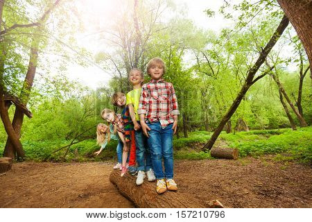 Five cute boys and girls standing on the log one after another in the forest
