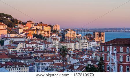 Cityscape of Lisbon Portugal seen from Miradouro Sao Pedro de Alcantara at sunset.