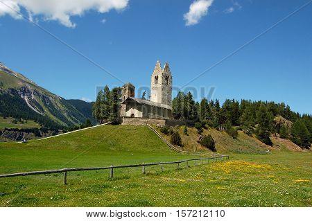 The ancient medieval church of San Gian (Saint John) in Celerina or Schlarigna small village in Engadine Switzerland Europe