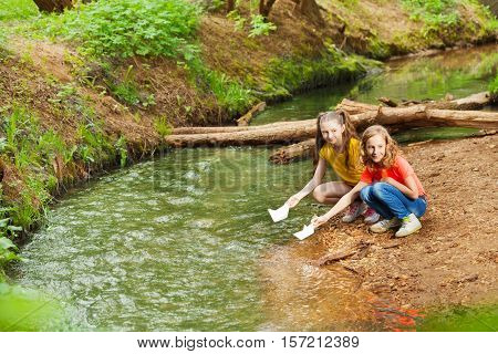 Portrait of two cute ten years old girls launching paper boats from riverside at sunny day