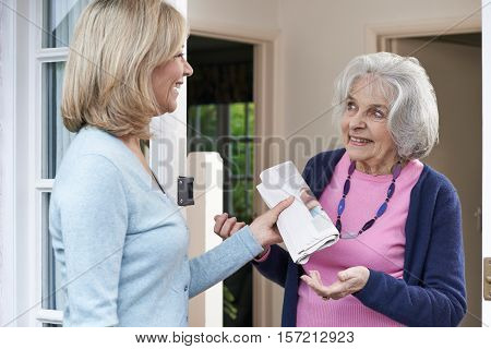Mature Woman Delivering Newspaper To Elderly Neighbour
