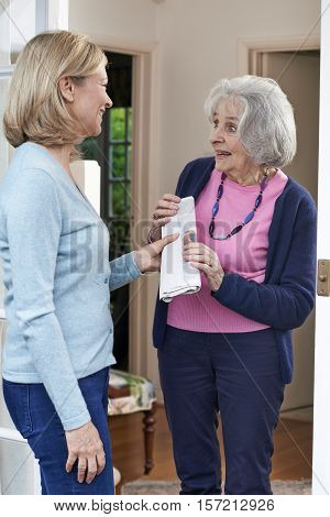 Friendly Woman Delivering Newspaper To Elderly Neighbour