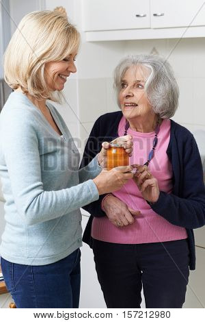 Woman Helping Senior Neighbor To Remove Jar Lid