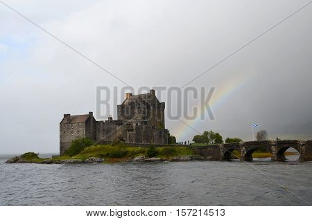Eilean Donan with an arching rainbow coming from the base.