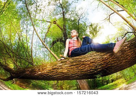 Bottom view portrait of teenage girl sitting on trunk of fallen tree at sunny day