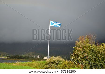 Scottish flag flying on the property of Eilean Donan Castle.