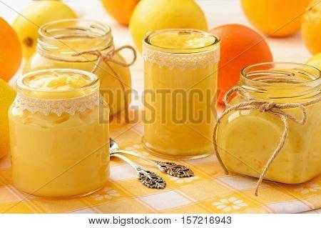 Orange curd and lemon curd (english citrus cream) in glass jars.