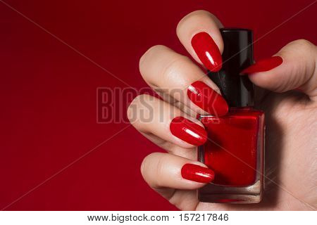 Female hand with red nails holds red nail polish on red background.