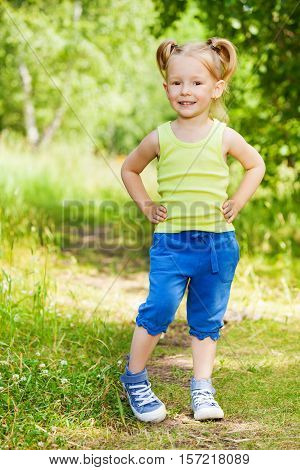Full-length portrait of beautiful little girl, standing akimbo on the path in the park