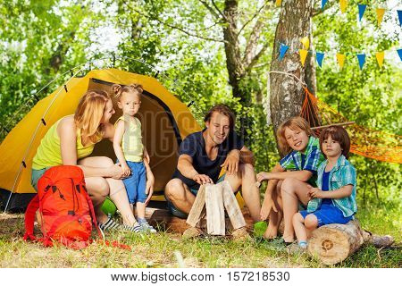 Active young family, parents and three kids, making camp fire with the fireplace log pieces in the woods