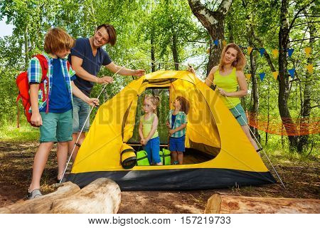 Happy young parents and three age-diverse kids putting up a tent on camping trip