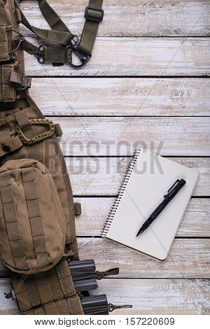 Notebook for notes pen battle belt and rifle ammo in magazine on wood background Top view
