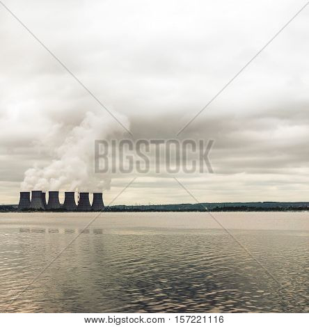 Nuclear power plant on the coast. Ecology disaster concept. Big clouds and water. Copy space
