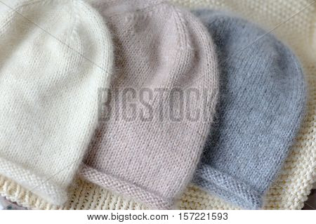 Three Hats Of The Same Style In Blue, Beige And White Made Of Wool On The Spokes