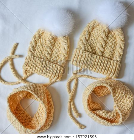 Two Yellow Sets Of Caps With A Fluffy Bobble And Snood