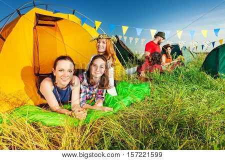 Portrait of three female campers relaxing in their tent at campsite