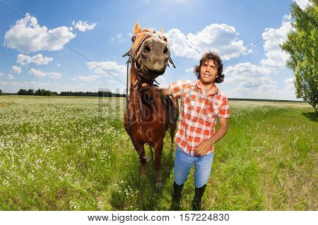 Young man holding his beautiful bay horse by a bridle at the flowery meadow in summer