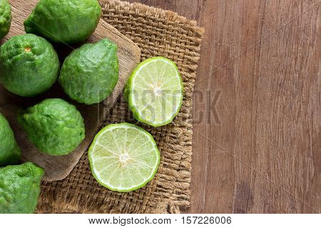 Close up fresh bergamot and bergamot slice on dark wood table background. bergamot on old wooden brown with copy space. (Bergamot or Kaffir lime)