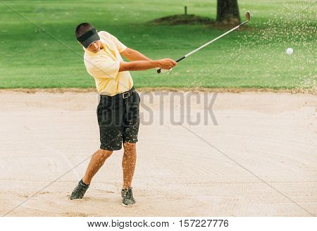 Golfer Playing From Sand Trap. Ball and grains of sand frozen in the air