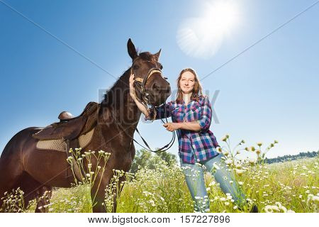 Portrait of happy young woman with her brown stallion in countryside