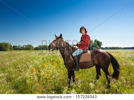 Side view portrait of happy male equestrian on bay horse at the flowery meadow in summer